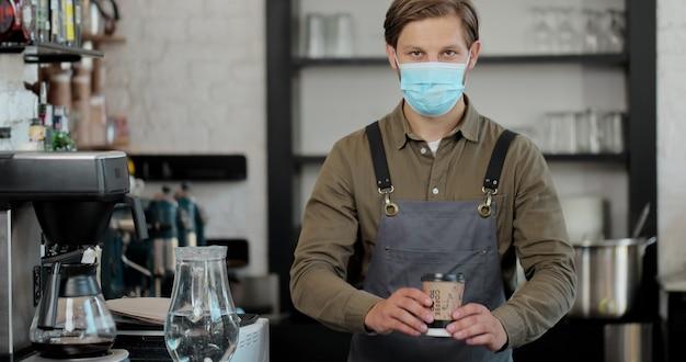 Ritratto di barista maschio caucasico bello in maschera medica e guanti che dà tazza di caffè alla macchina fotografica e sorridente. barista che passa bere il caffè da asporto nella caffetteria.
