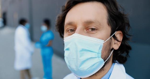Ritratto del medico caucasico dell'uomo bello nella mascherina medica che guarda l'obbiettivo. primo piano del medico maschio nella protezione delle vie respiratorie. colleghi di medici afroamericani sullo sfondo.