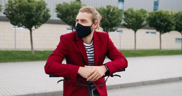 Ritratto del giovane bello caucasico in maschera che sta all'aperto, che si appoggia sulla bici o sul motorino elettrico e sorride alla macchina fotografica. bello maschio elegante in posa alla telecamera in bicicletta. concetto di pandemia.