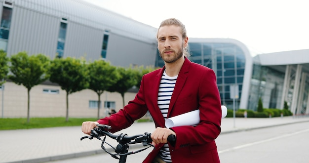 Ritratto di giovane uomo caucasico bello in giacca rossa in piedi all'aperto con bici o scooter elettrico e guardando la fotocamera. bel ragazzo elegante alla bicicletta che tiene carta o disegno sulla strada della città