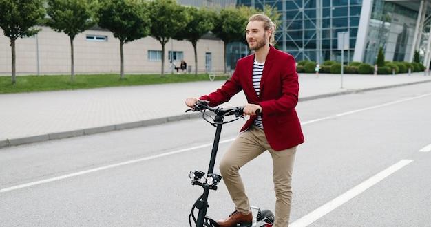 Ritratto del giovane bello caucasico in giacca rossa in piedi all'aperto con bici o scooter elettrico e sorridendo alla telecamera. bel ragazzo elegante in bicicletta sulla strada cittadina.