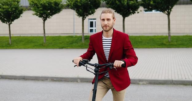 Ritratto di giovane uomo caucasico bello in giacca rossa in piedi all'aperto con scooter elettrico e sorridere alla telecamera. bel ragazzo elegante al veicolo sulla strada cittadina. colpo di dolly. ingrandimento.
