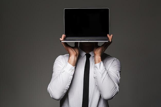 Ritratto di lavoratore di ufficio maschio caucasico in posa tenendo il computer portatile con schermo copyspace invece della sua testa, isolato sopra il muro grigio
