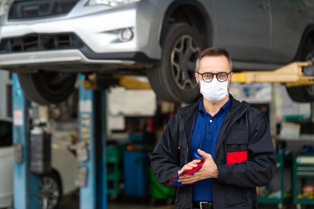 Ritratto dell'uomo caucasico che pulisce le mani con un panno e indossa coronavirus di protezione della maschera facciale medica .. meccanico di esperienza che lavora nel garage di riparazione di automobili.