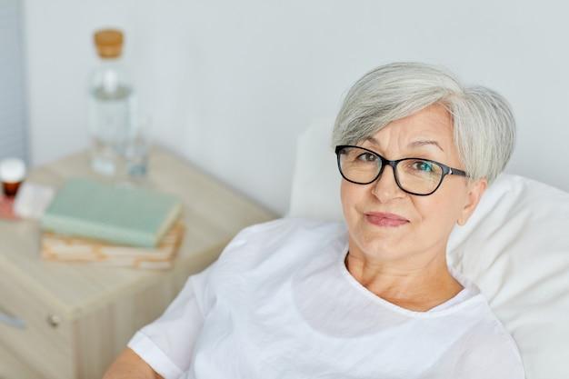 Ritratto di donna matura caucasica indossando occhiali da vista recupero in reparto ospedaliero