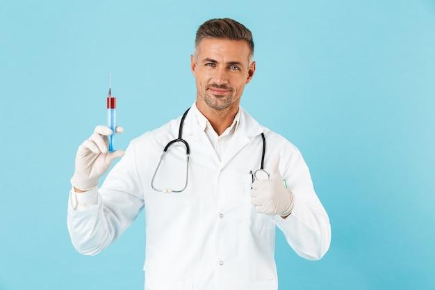 Ritratto del medico caucasico con lo stetoscopio in guanti che tengono la siringa, in piedi isolato sopra la parete blu