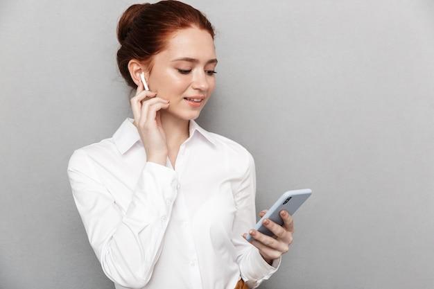 Ritratto di una donna d'affari caucasica rossa 20s che indossa auricolari che tiene e guarda lo smartphone in ufficio isolato su grigio