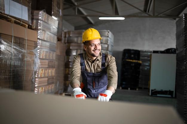 Ritratto del lavoratore di magazzino sorridente caucasico che lavora al carrello elevatore manuale nel ripostiglio.
