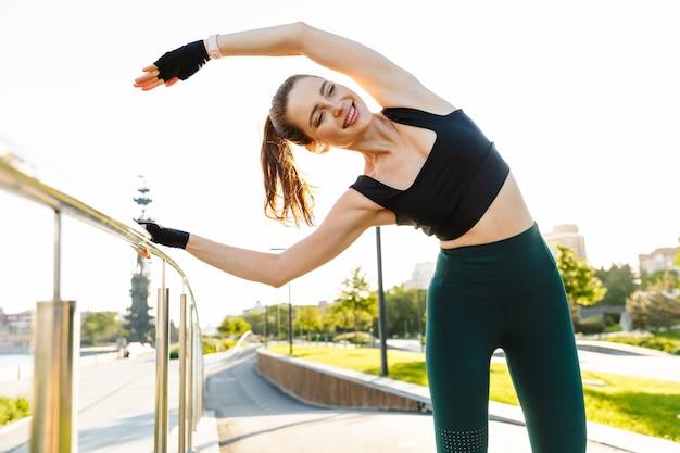 Ritratto di donna sportiva caucasica che indossa tuta da ginnastica appoggiata alla ringhiera e allunga il suo corpo durante l'allenamento nel parco verde