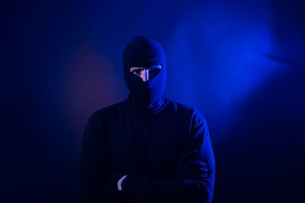 Ritratto di ladro caucasico con cappuccio. include le luci della polizia. include le luci della polizia.