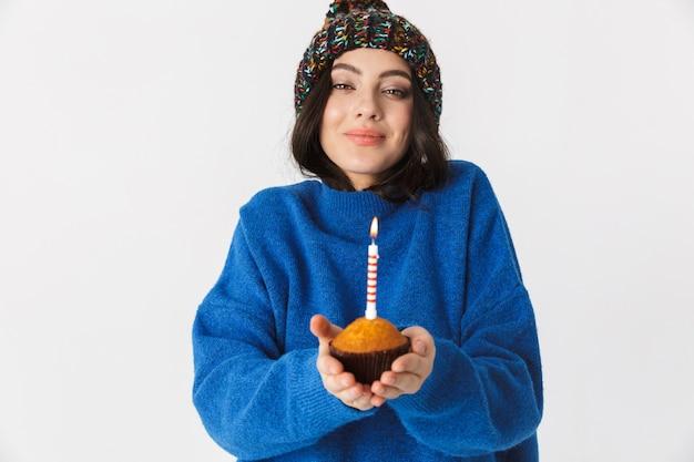 Ritratto di donna caucasica indossando il cappello invernale tenendo la torta di compleanno con una candela in piedi, isolato su bianco
