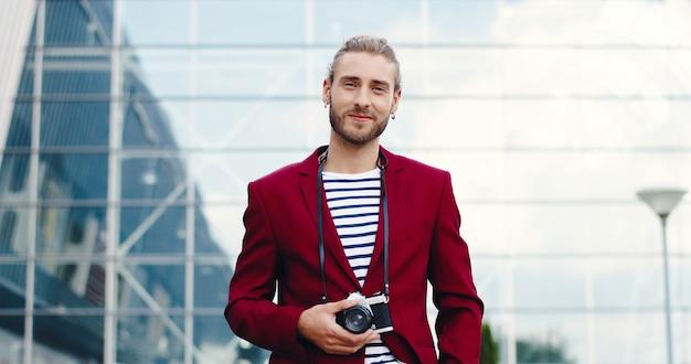 Ritratto di giovane uomo bello caucasico con macchina fotografica che guarda l'obbiettivo e sorridente all'aperto. elegante fotografo maschio di bell'aspetto in strada. scattare foto concetto. città urbana. costruzione moderna.