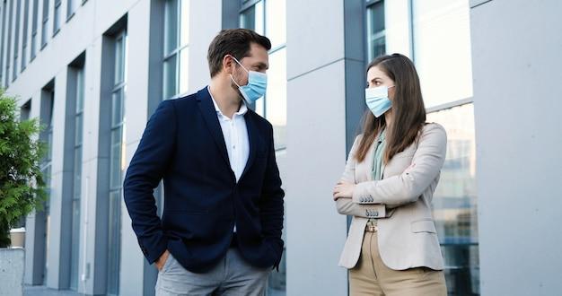 Ritratto di giovane caucasico uomo e donna in stile business e maschere mediche in piedi a distanza sociale e guardando la fotocamera. uomo d'affari e donna d'affari all'aperto durante la pandemia.
