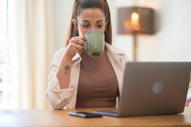Ritratto di giovane donna caucasica che lavora e che digita sulla tastiera del computer portatile - ufficio e concetto di lavoro di lavoro intelligente per azienda aziendale professionale o dipendente