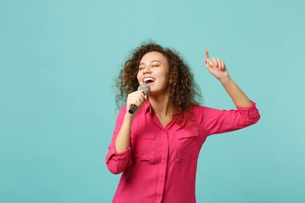 Il ritratto della ragazza africana affascinante in vestiti casuali che balla canta la canzone in microfono isolato sul fondo blu della parete del turchese in studio. concetto di stile di vita di emozioni sincere della gente. mock up copia spazio.
