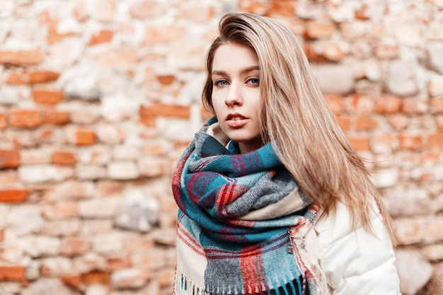 Ritratto di un'affascinante bella giovane donna con gli occhi azzurri con una calda sciarpa a scacchi alla moda e giacca bianca alla moda autunno sullo sfondo di un vecchio muro di mattoni vintage. ragazza attraente