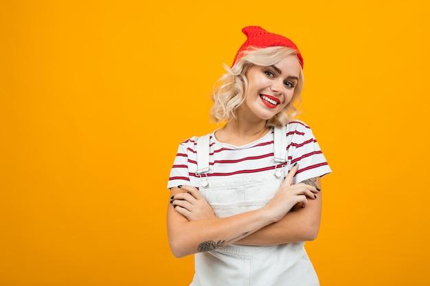 Ritratto di un'affascinante ragazza bionda con un bel trucco con labbra rosse in una maglietta a righe e salopette di jeans sorridente su uno sfondo giallo