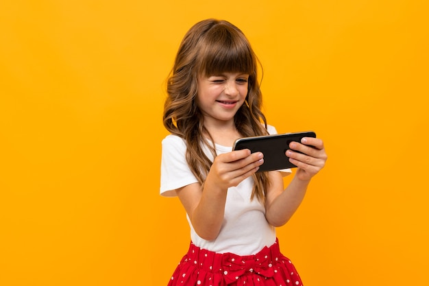 Ritratto di affascinante ragazza caucasica con lunghi capelli castani e bel viso in abito bianco e rosso guarda un film o cartoni animati con il suo telefono e sorrisi