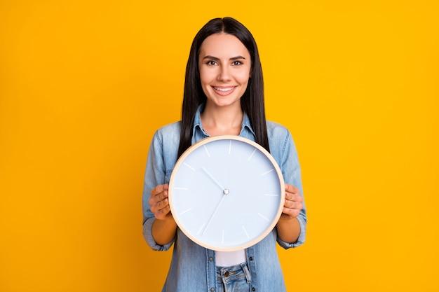 Ritratto di affascinante ragazza allegra che tiene in mano mostrando l'orologio rotondo