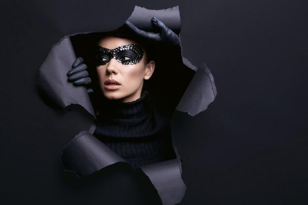 Ritratto di affascinante donna bruna elegante in maglione nero a collo alto e maschera di paillettes guarda attraverso uno studio strappato