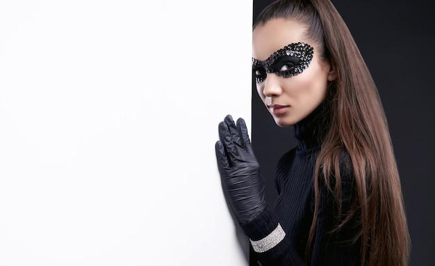 Ritratto di affascinante donna bruna elegante in maglione dolcevita nero e paillettes maschera in posa vicino al muro bianco in studio