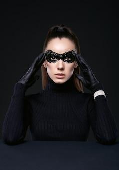 Ritratto di affascinante donna bruna elegante in maglione dolcevita e paillettes maschera in posa sul nero in studio