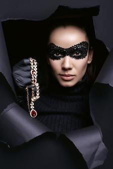 Ritratto di affascinante donna bruna elegante in maglione dolcevita e maschera di paillettes con guanti neri in posa con una collana di diamanti rubata
