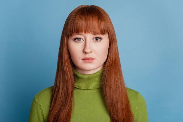 Ritratto di una ragazza affascinante e concentrata che guarda la telecamera su sfondo blu