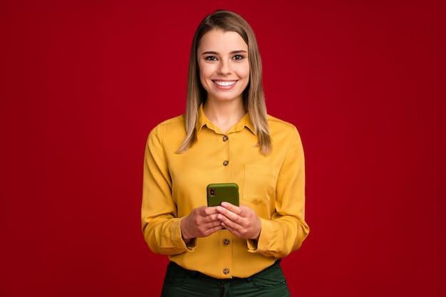 Ritratto di un'affascinante ragazza concentrata che indossa una camicetta gialla utilizzando un dispositivo gadget