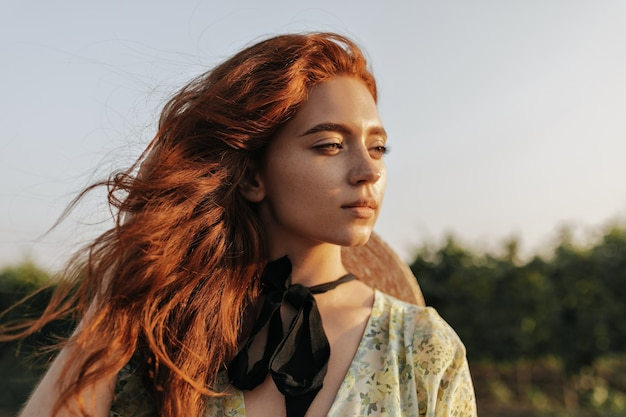 Ritratto di una ragazza affascinante con capelli color zenzero brillante, graziose lentiggini e bende scure sul collo che guardano lontano e posano all'aperto