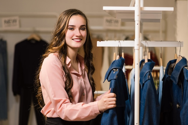 Ritratto di affascinante gioiosa femmina venditore o cliente presso il negozio di vestiti