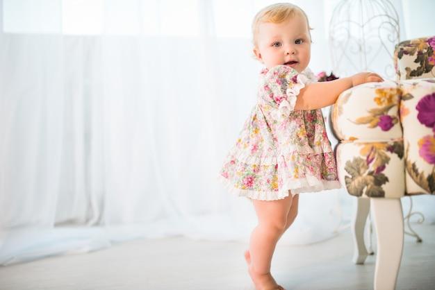 Ritratto di una bambina affascinante in un bel vestito in piedi vicino a una sedia con una stampa floreale