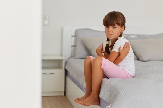 Ritratto di affascinante ragazza triste offesa che indossa maglietta bianca e pantaloncini rosa, guardando la telecamera, piangendo, sentendosi addolorata, posando sul letto in una stanza luminosa da sola.
