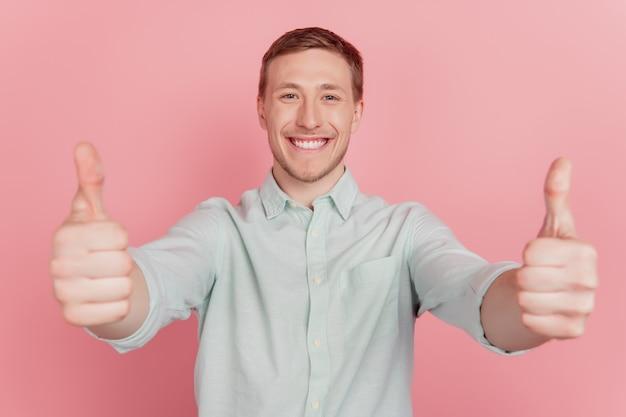 Il ritratto di un affascinante consigliere positivo alza il pollice in su concorda la raccomandazione su sfondo rosa
