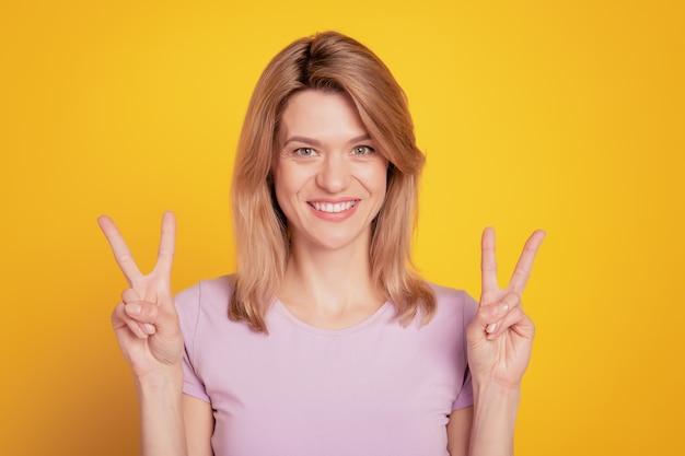 Il ritratto di una signora allegra e positiva affascinante dimostra segni di v su sfondo giallo
