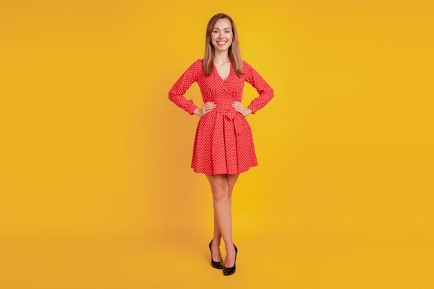 Ritratto di affascinante donna positiva mani fianchi indossare mini abito rosso tacchi alti sulla parete gialla