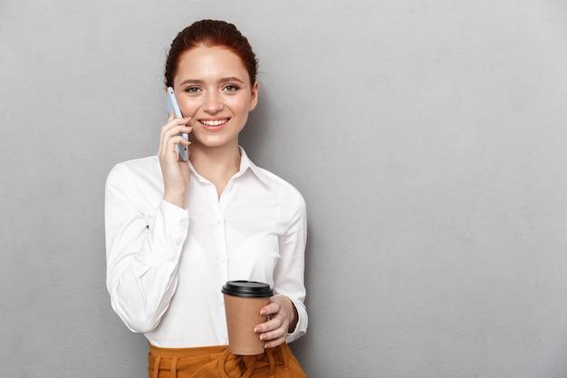 Ritratto di affascinante donna d'affari rossa 20s in abbigliamento formale che utilizza smartphone in ufficio e beve caffè da asporto dal bicchiere di plastica isolato su grigio