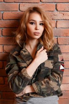 Ritratto di un'affascinante giovane donna sexy con bellissimi occhi in una giacca verde mimetica militare alla moda e una maglietta grigia vicino al muro di mattoni. ragazza bionda alla moda riccia. moda moderna