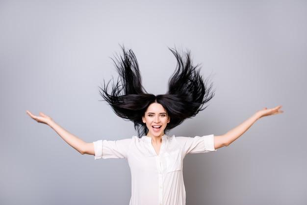 Ritratto di affascinante signora sorridente in camicia bianca con capelli volanti