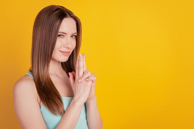 Il ritratto di affascinanti dita civettuole tentatrici mostrano il gesto della pistola su sfondo giallo