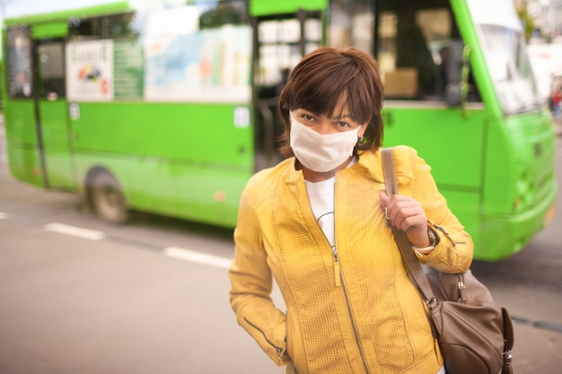 Ritratto di affascinante donna di mezza età seria non identificata in una maschera medica bianca in un contesto urbano