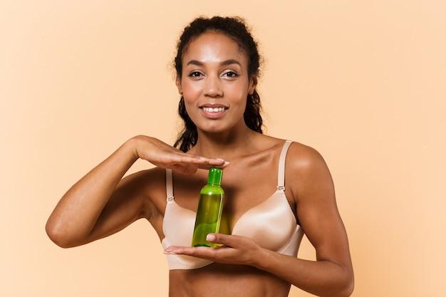 Ritratto di donna affascinante che indossa lingerie bianca tenendo la bottiglia con cosmetici, mentre in piedi isolato sul muro beige