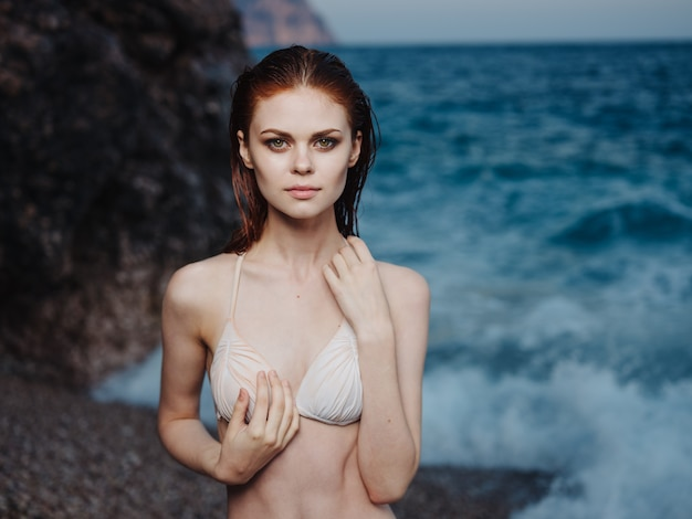 Ritratto di modello di costume da bagno bianco donna affascinante e spiaggia di schiuma bianca mare blu.