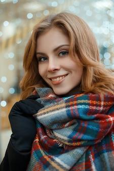 Ritratto di una donna affascinante con capelli biondi e bel sorriso in un elegante cappotto nero in guanti neri con una calda sciarpa di lana