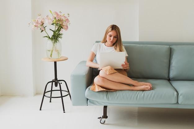 Ritratto di giovane donna affascinante con laptop che lavora a casa mentre è seduto sul divano