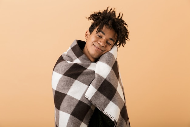 Ritratto del ragazzo afroamericano allegro che sorride mentre copre in coperta, isolata sopra la parete beige