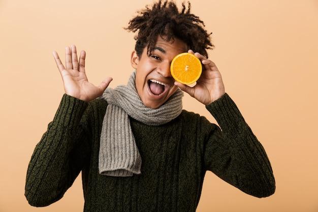 Ritratto di allegro ragazzo afroamericano che indossa un maglione e sciarpa che tiene mezza arancia, isolata sopra la parete beige