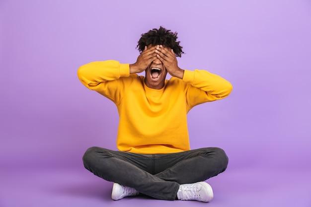 Ritratto di un allegro ragazzo afroamericano seduto sul pavimento con le gambe incrociate e che copre gli occhi con le mani, isolato su sfondo viola