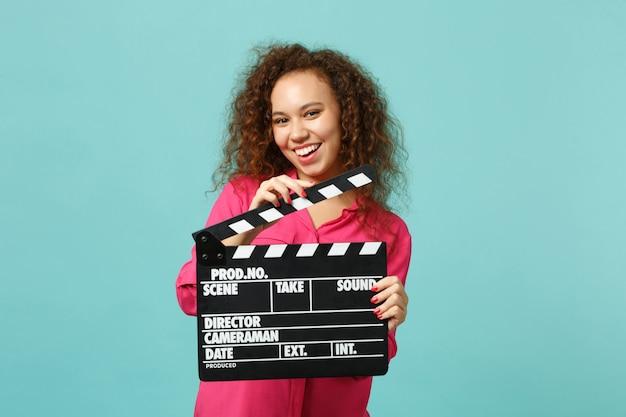 Ritratto di allegra ragazza africana in abiti casual che tiene il classico film nero che fa ciak isolato su sfondo blu turchese. concetto di stile di vita di emozioni sincere della gente. mock up copia spazio.
