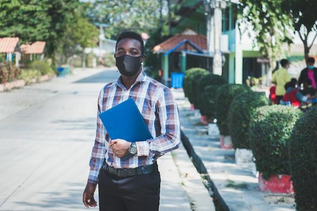 Ritratto di allegro insegnante africano in maschera in piedi all'aperto a scuola